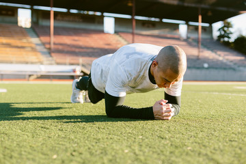 Athletic Man In Plank Position On Turf Field During Workout Routine