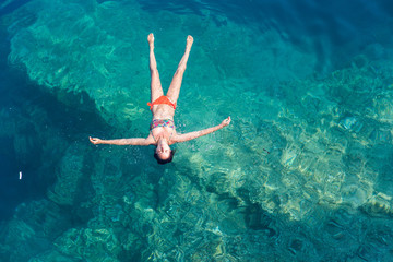 Beautiful young woman in a bikini floating in the ocean water and relaxing