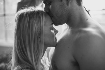 Young shirtless man kissing girlfriends forehead in industrial loft