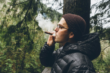 Young Man Smoking Cigar Outside In Forest Air