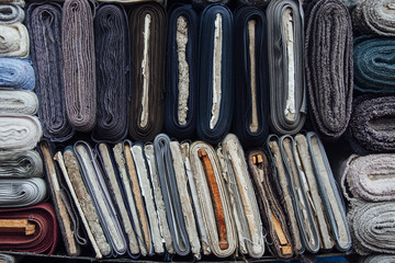 Rolls of textile on display on a wholesale market.