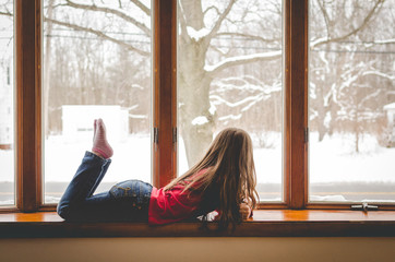 Girl lying beside snowy window