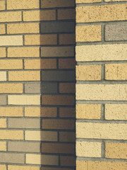 Beige and brown brick wall, casting shadow