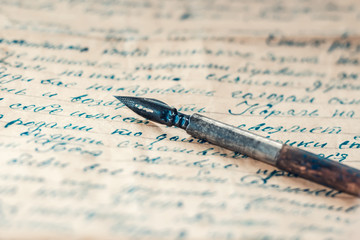 Old fountain pen on vintage letter sepia blue
