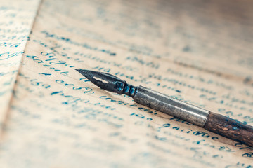 Old fountain pen on vintage letter sepia blue background
