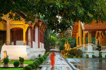 Monk walking under an umbrella at the Wat Phra Singh Temple, Chiang Mai, Thailand. Chiang Mai's most revered temple.