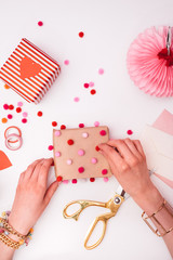 Woman Decorating Valentine's Day Gift With Pompons