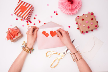 Woman Putting Red Hearts in a Pink Envelope