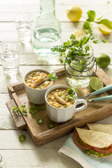 Delicious corn and crab summer chowder for two people on wooden tray.