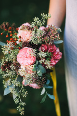 Woman holding a lovely bouquet of pink peonies and eucalyptus