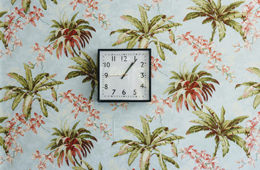Square clock on wall decorated with beautiful wallpaper