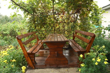 wooden oak table with benches in the garden in the fall