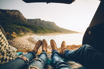 point of view of a couple lying in the back of their car enjoying sunset coastal view