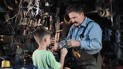 Close view of grandpa carpenter shows his grandson different tools in a small workshop.