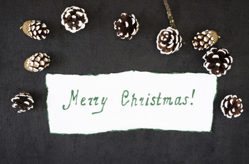 Christmas decorations with pine cones and a congratulatory inscription on the paper on a dark background