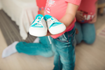 The girl is holding the shoes of her future sister.