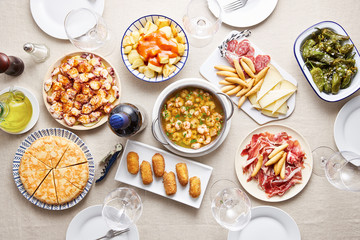 Traditional spanish dishes with empty glasses on table