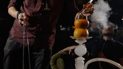 Young hookahman changing the coals in the hookah while men is smoking