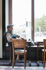 Profile of Elderly Caucasian Man With Long Beard Sitting in Stylish Restaurant