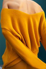 back of young woman with yellow sweater