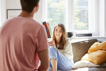Happy Young Woman Talking With Man At Home