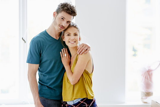 Loving Couple Standing Arm Around At Home