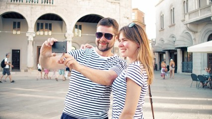 Young cheerful couple making selfie on vacation