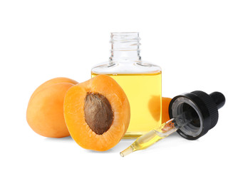 Bottle of apricot oil with fresh fruit on white background