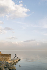 Woman in warrior pose at waterfront