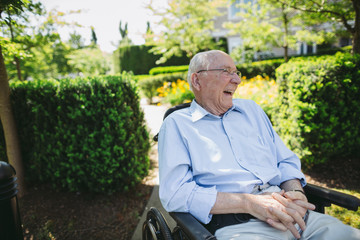 Happy, fun loving elderly couple outside in garden using wheelchair
