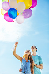 Teenage couple smiling holding colorful balloons over blue sky.