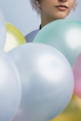 Close-up of girl's face near balloons