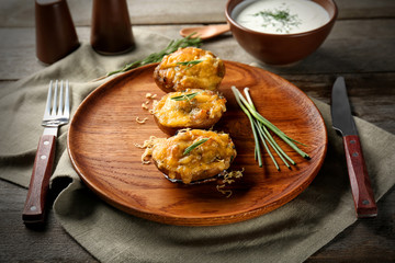 Baked stuffed potatoes on wooden plate
