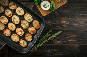Grill pan with delicious baked potato slices on wooden background