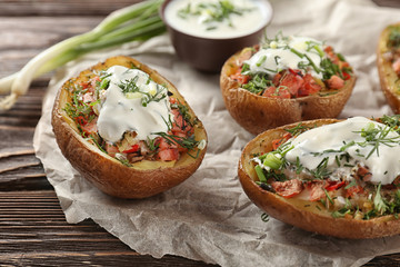 Baked stuffed potatoes on wooden table