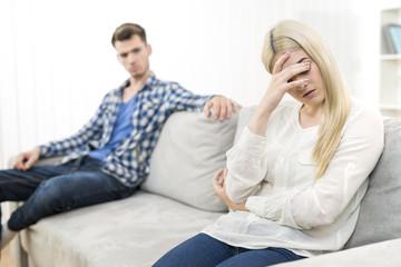 The sad woman sit near the man on the sofa