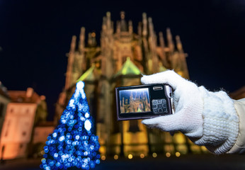 Closeup on woman in Prague taking photo with digital camera