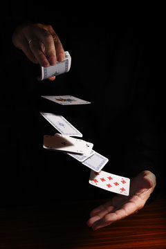 throwing cards from one hand to the other against a black background with copy space, business metaphor or concept for new start, destiny, and gamble, copy space, vertical