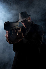 detective or criminal with gun on foggy night background