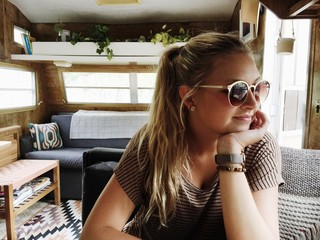 Attractive young woman sitting in renovated trailer