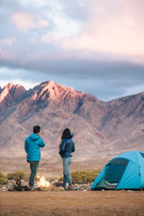 Outdoorsy hiking couple at their camp fire in a rugged mountain landscape
