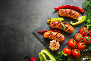 Fried bbq sausages with  vegetables at black background. Top view with copy space.