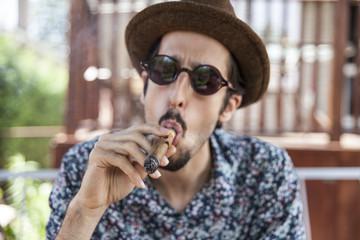 Young man wearing fedora smoking cigar