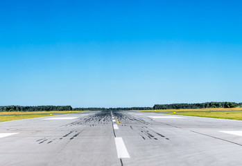 Runway at the airport with good weather and clear blue sky.