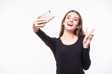 Gorgeous young woman in street style clothes taking selfie with mobile phone isolated over white background