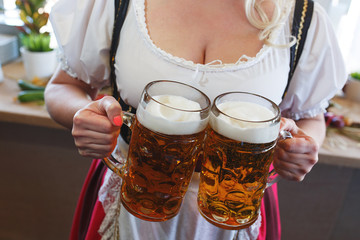 Girl in a traditional dress with a big breasts and deep neckline holds full mugs of beer.