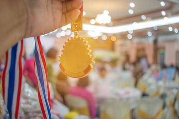 Businessman hands raised and holding gold medals with Thai ribbon against convention hall background to show success in business, Winners success award concept.