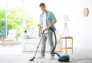 Man cleaning white carpet with vacuum in living room