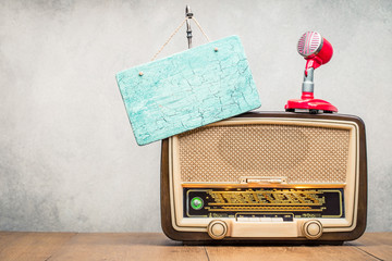 Retro wooden broadcast radio receiver with green eye light, studio microphone and aged signboard blank front concrete wall background. Listen music concept. Vintage instagram old style filtered photo