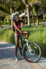 fit young woman on bike drinking water to hydrate